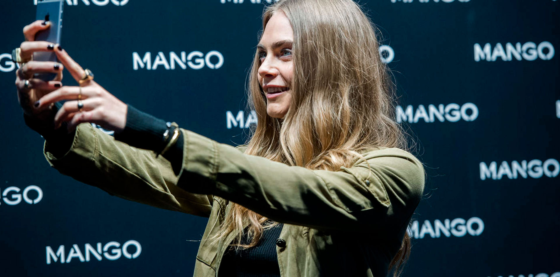 Cara Delevingne taking a picture with Mango's Something in common app